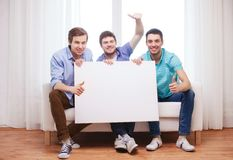 Amigos masculinos felizes com placa branca vazia em casa Fotografia de Stock