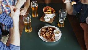 Amigos masculinos felizes que bebem a cerveja na barra ou no bar vídeos de arquivo