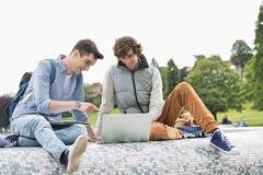 Amigos masculinos jovenes de la universidad con el ordenador portátil que estudian junto en parque Fotos de archivo libres de regalías