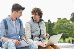 Amigos masculinos jovenes de la universidad con el ordenador portátil que estudian junto en parque Imágenes de archivo libres de regalías