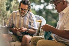 Amigos masculinos jubilados que hacen hacer punto para el pasatiempo imagen de archivo