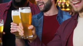 Amigos masculinos multiétnicos que tintinean los vidrios de cerveza, igualando en pub, tiempo libre almacen de metraje de vídeo