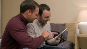 Amigos masculinos novos e assento no sofá e utilização da tabuleta, duscussing algo e o riso Fotos de Stock Royalty Free