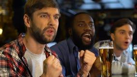 Amigos masculinos que apoyan al equipo de deportes en el pub, decepcionado sobre la bola fuera de juego metrajes