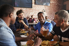 Amigos masculinos que comem para fora na barra de esportes com telas dentro atrás fotos de stock royalty free
