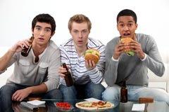 Amigos masculinos que comen las hamburguesas Foto de archivo