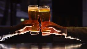Amigos masculinos que hacen clic los vidrios de cerveza, relajándose después de semana laboral dura, tarde almacen de metraje de vídeo