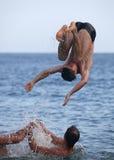 Amigos masculinos que juegan en el mar Foto de archivo libre de regalías