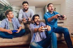 Amigos masculinos que juegan a los videojuegos en casa y que se divierten imagen de archivo libre de regalías