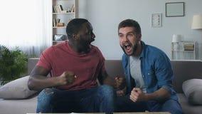 Amigos masculinos que olham o futebol, rujindo alto após ter ganhado o objetivo em semi-final filme