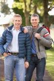Amigos masculinos que recorren en parque del otoño Imágenes de archivo libres de regalías