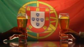 Amigos masculinos que sostienen los vidrios de cerveza, bandera portuguesa en el fondo, celebración almacen de metraje de vídeo