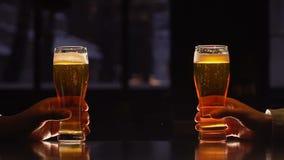 Amigos masculinos que sostienen los vidrios de cerveza, tiempo libre en casa, igualando la relajación almacen de video