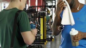 Amigos masculinos que tienen conversación en gimnasio, un cóctel de la proteína que se sostiene y teléfono metrajes