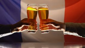 Amigos masculinos que tintinean los vasos de cerveza, bandera francesa en el fondo, celebración metrajes