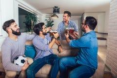 Amigos masculinos que ven la TV y que animan juegos del deporte en el sofá en casa foto de archivo libre de regalías