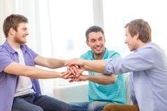 Amigos masculinos sonrientes con las manos junto en casa Imágenes de archivo libres de regalías