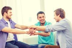 Amigos masculinos sonrientes con las manos junto en casa Imagenes de archivo