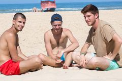 Amigos masculinos sonrientes de Fgroup en playa Fotografía de archivo