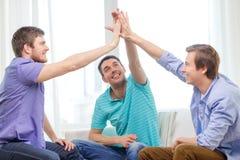 Amigos masculinos sonrientes que dan el alto cinco en casa Imagen de archivo