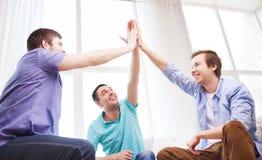 Amigos masculinos sonrientes que dan el alto cinco en casa Imágenes de archivo libres de regalías