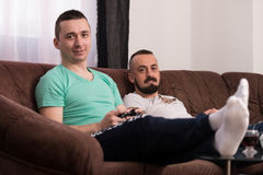 Amigos masculinos sonrientes que juegan a los videojuegos en casa Imágenes de archivo libres de regalías