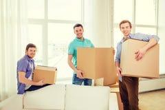 Amigos masculinos sonrientes que llevan las cajas en el nuevo lugar Foto de archivo libre de regalías