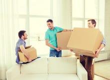 Amigos masculinos sonrientes que llevan las cajas en el nuevo lugar Fotos de archivo libres de regalías
