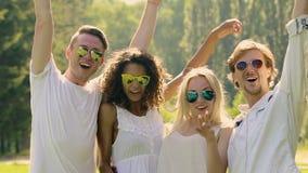 Amigos masculinos y femeninos emocionados que disfrutan de las manos felices de la vida, del aumento y el agitar para arriba almacen de metraje de vídeo