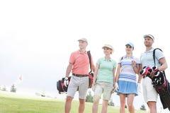 Amigos masculinos y femeninos que se oponen en el campo de golf al cielo claro foto de archivo libre de regalías