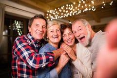 Amigos mayores con el smartphone que toma el selfie en el tiempo de la Navidad fotos de archivo