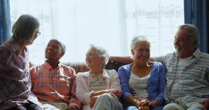 Amigos mayores felices que obran recíprocamente con uno a mientras que se relaja en el sofá 4k almacen de video