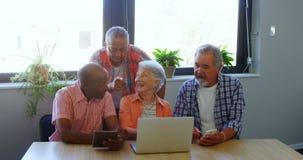 Amigos mayores felices que obran recíprocamente con uno a mientras que usa el ordenador portátil 4k almacen de metraje de vídeo