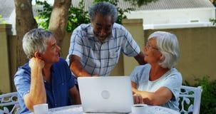 Amigos mayores felices que obran recíprocamente con uno a mientras que usa el ordenador portátil 4k metrajes