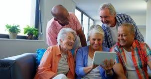 Amigos mayores felices que usan la tableta digital en el sofá almacen de metraje de vídeo