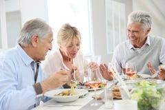 Amigos mayores que almuerzan en casa Foto de archivo libre de regalías