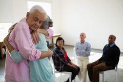 Amigos mayores que consideran el abarcamiento del hombre y de la mujer Imágenes de archivo libres de regalías