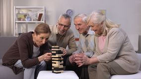 Amigos mayores que construyen la torre a partir del tiempo libre de los cubos de madera en clínica de reposo metrajes