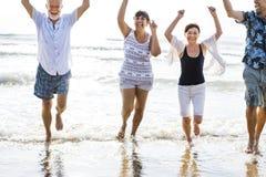Amigos mayores que se divierten en la playa imagen de archivo