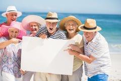 Amigos mayores que sostienen el papel en blanco Imágenes de archivo libres de regalías