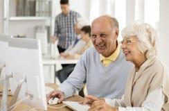 Amigos mayores que trabajan en el ordenador fotografía de archivo