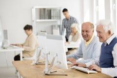 Amigos mayores que trabajan en los ordenadores fotografía de archivo