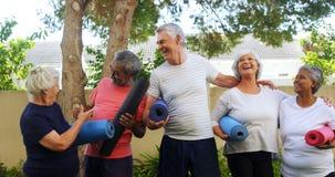 Amigos mayores sonrientes que sostienen la estera del ejercicio y que obran recíprocamente con uno a 4k almacen de video