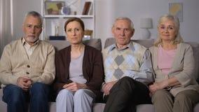 Amigos mayores trastornados que se sientan en el sofá y que miran la cámara, problemas sociales almacen de video
