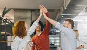 Amigos milenares multirraciais que dão altamente cinco no escritório fotos de stock royalty free