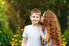 Amigos muchacho y abarcamiento y susurros de la muchacha en parque de la primavera Imágenes de archivo libres de regalías