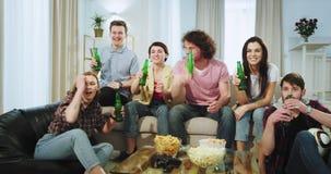 Amigos muito entusiasmados que preparam-se para olhar um fósforo de futebol na tevê no meio de uma sala de visitas eles cerveja b vídeos de arquivo