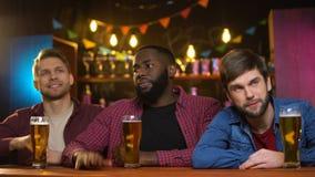 Amigos multiétnicos ansiosos infelices, partido perdidoso del equipo preferido, tiempo en pub almacen de metraje de vídeo