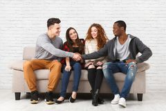 Amigos multiétnicos felices, gente casual que se sienta en el sofá dentro y risa Imagen de archivo libre de regalías