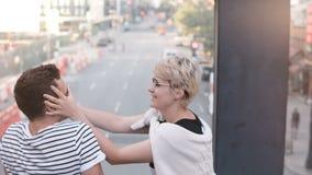 Amigos multiétnicos jovenes hermosos que se sientan en un puente que disfruta de la opinión preciosa de la calle de Nueva York, c almacen de metraje de vídeo